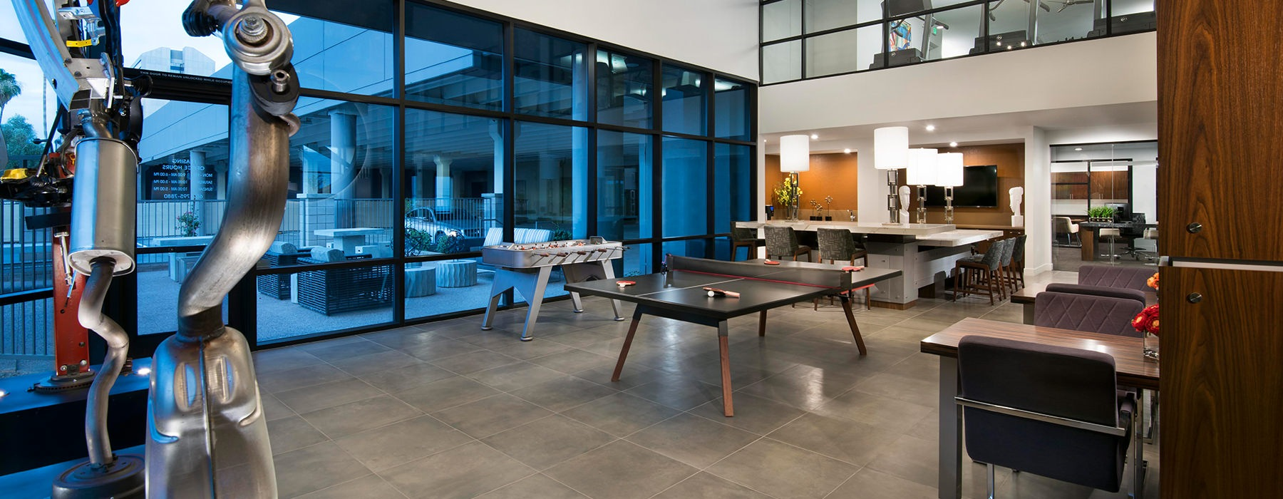 Resident clubhouse with ping pong table and floor-to-ceiling windows